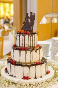 mehrstöckige Hochzeitstorte mit Früchten und Schokoladefigur