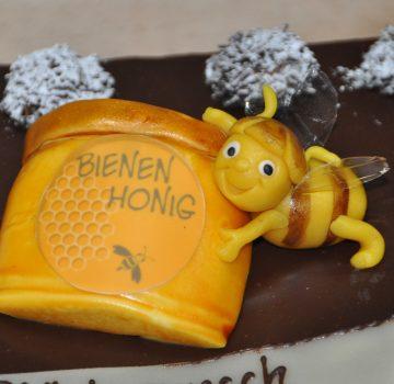Ausschnitt einer Geburtstagstorte; Biene am Honigglas