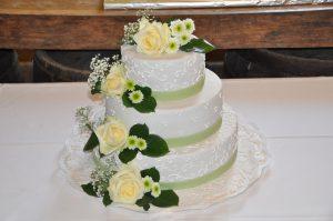 Hochzeitstorte mit echten Blumen und weißen Elementen